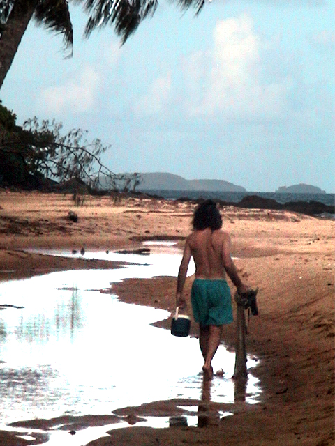 At Bingil Bay in Northern Queensland, Australia. Here I am walking up the beach at low tide after netting small fish for bait.
