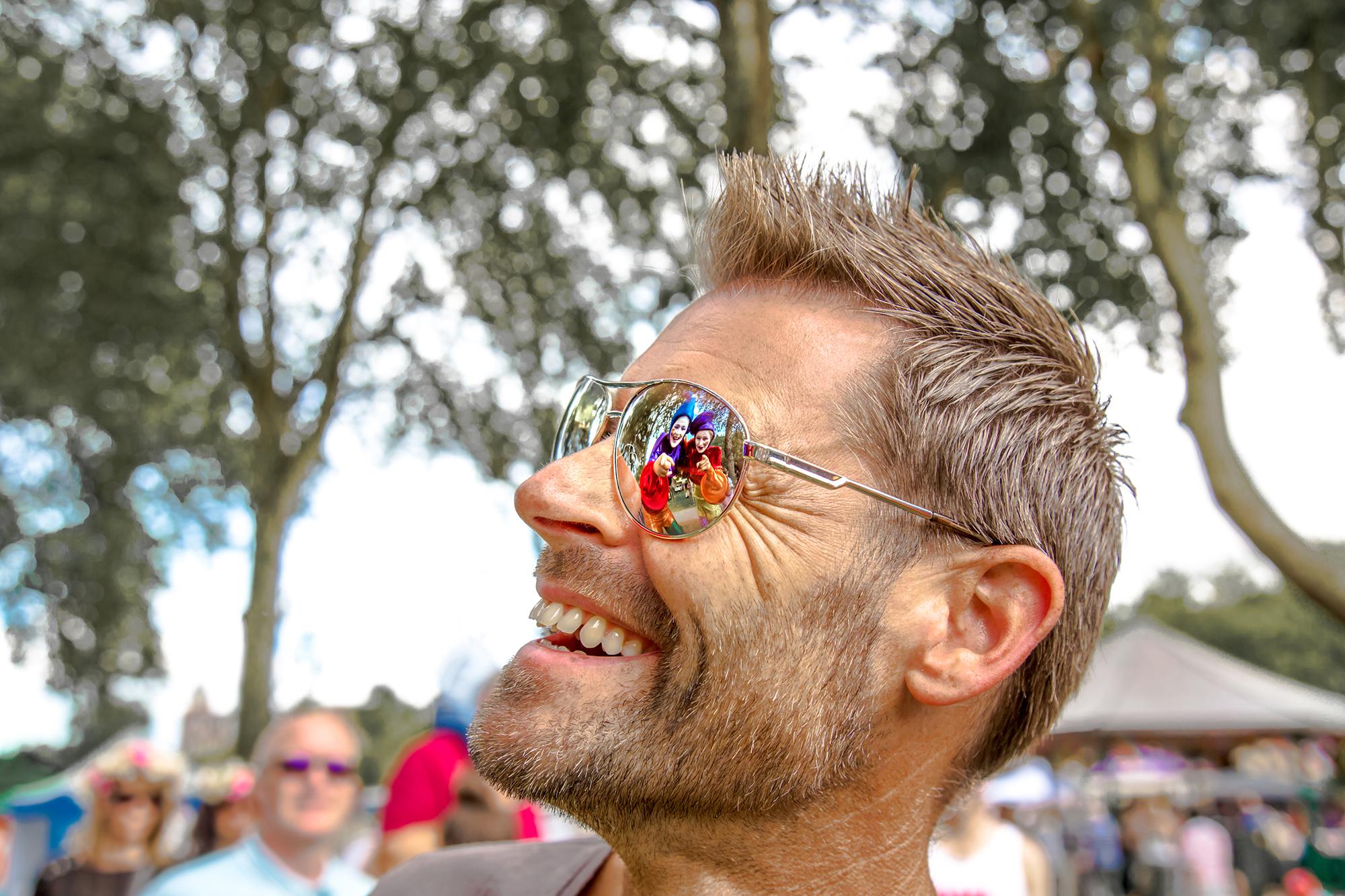 Stilt Walker Reflected in Glasses