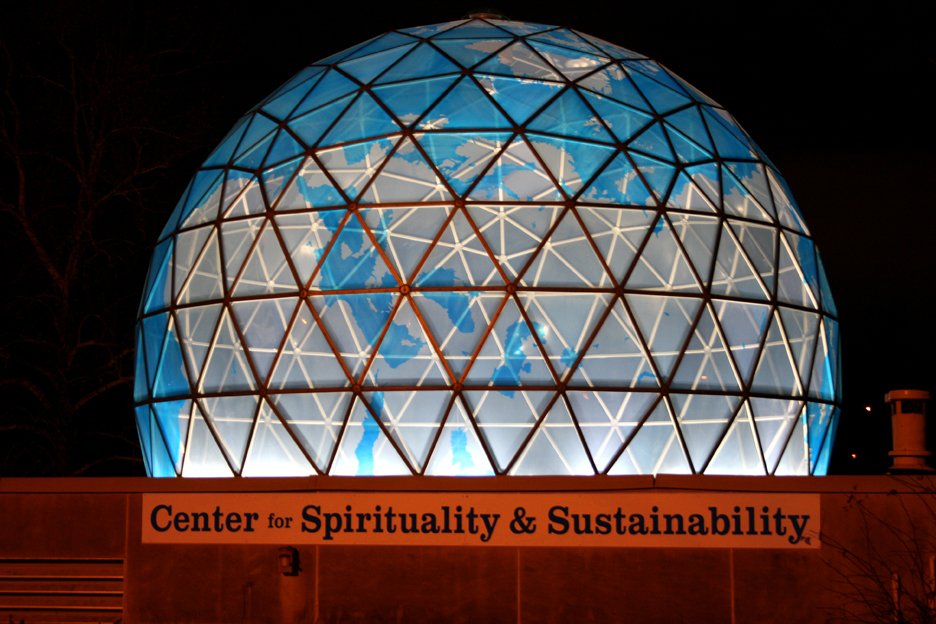 The Center's miniature Earth dome illuminated at night, straddling the 90th meridian