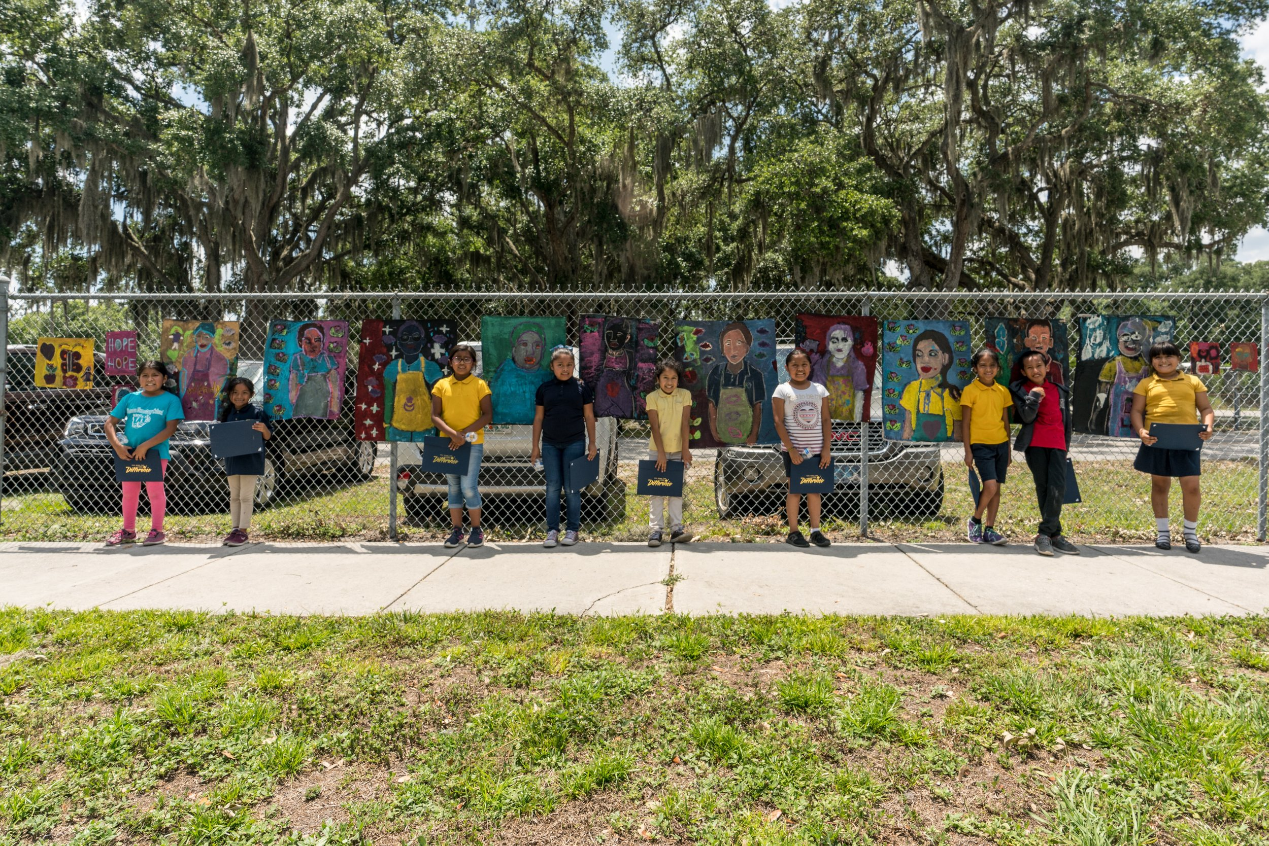 Our Mobile Art Factory teaches free art classes to the students at Wimauma Elementary. Here the students display their public art works with teacher Bryant Martinez.