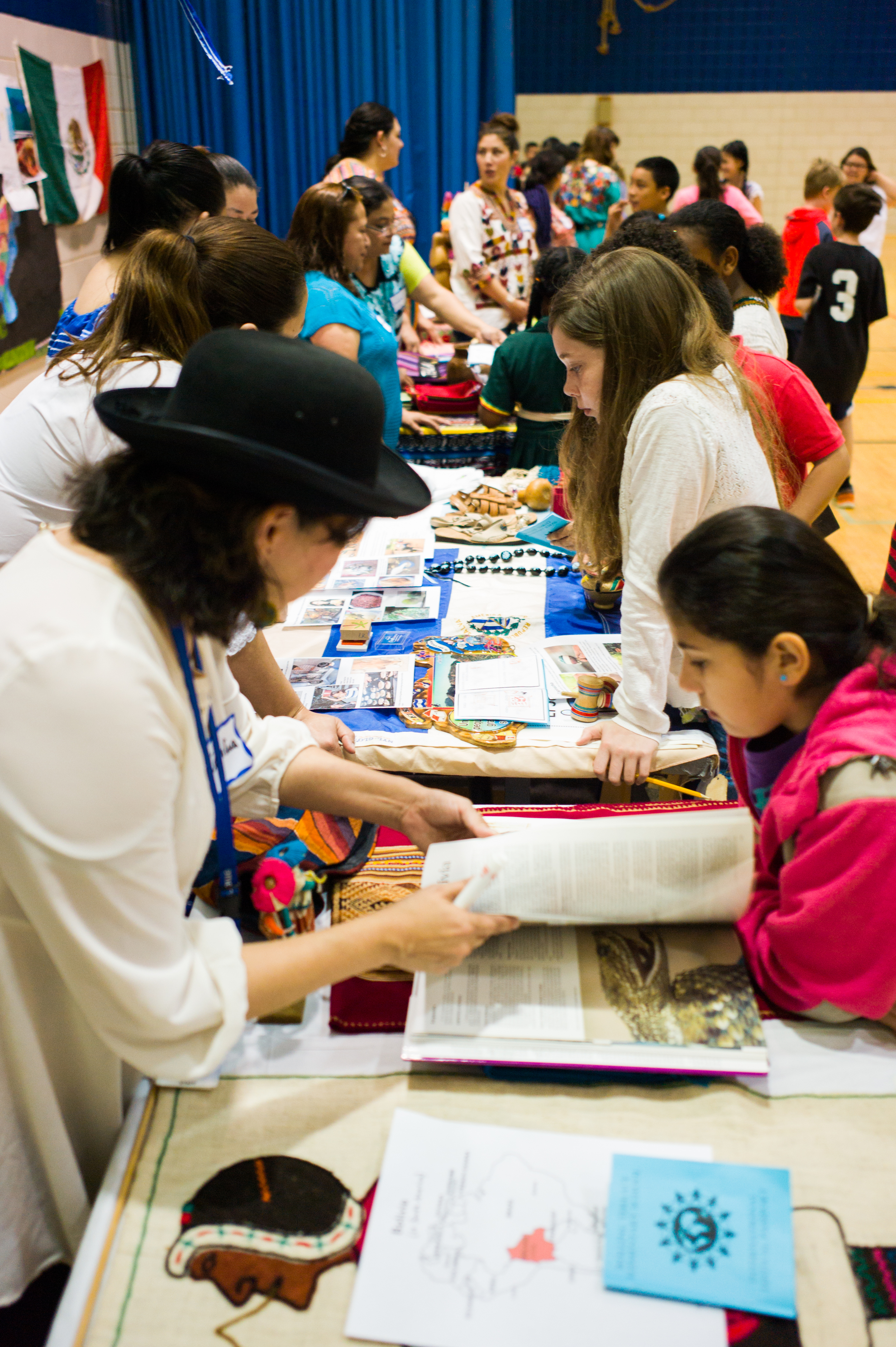 The gym was filled with tables from countries all over the world. Students could hold objects from different countries (artwork, ceramics, skis, dolls, etc.), try out games (like using the capirucho from El Salvador), play musical instruments (like the pellet drum from China or a Ngoma drum from Namibia), look at clothing, make a beaded bracelet (from Kenya), try out using chopsticks and much, much more.