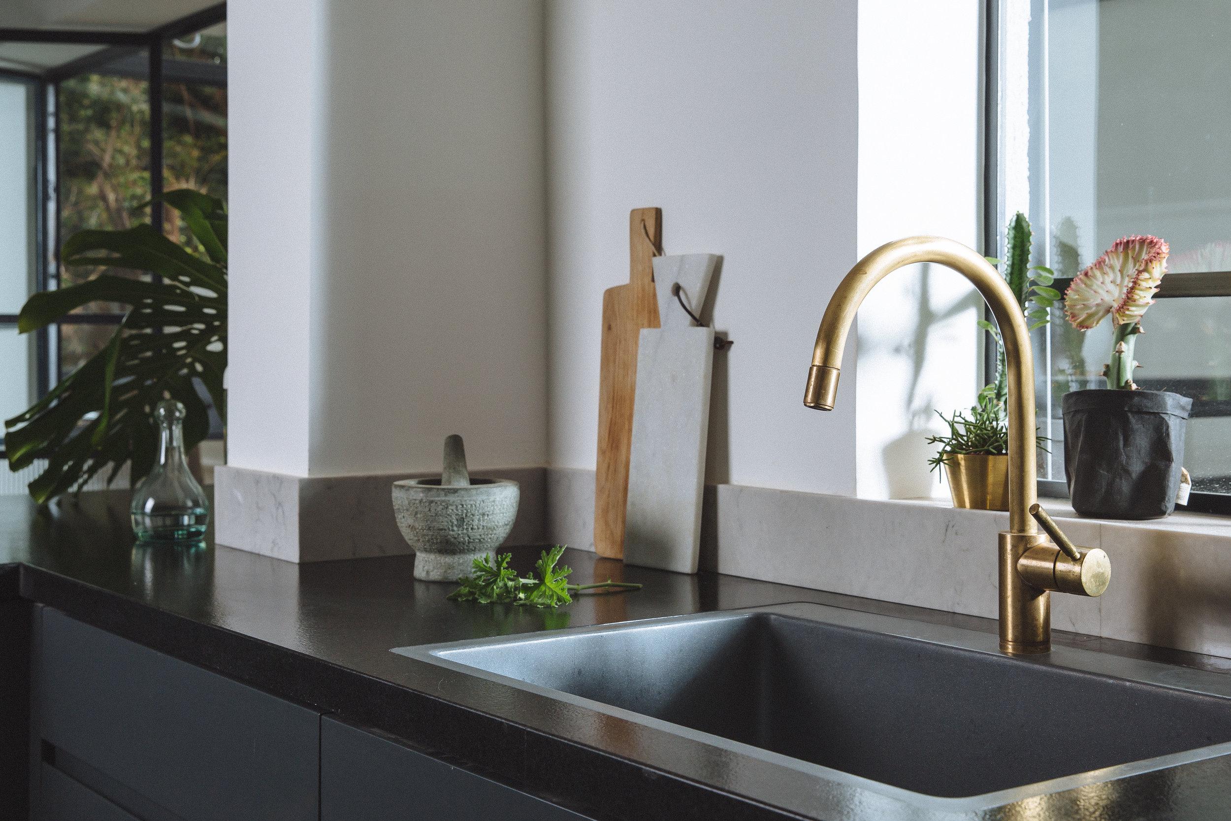 Dark themed kitchen, minimalist and elegant. Brass faucet