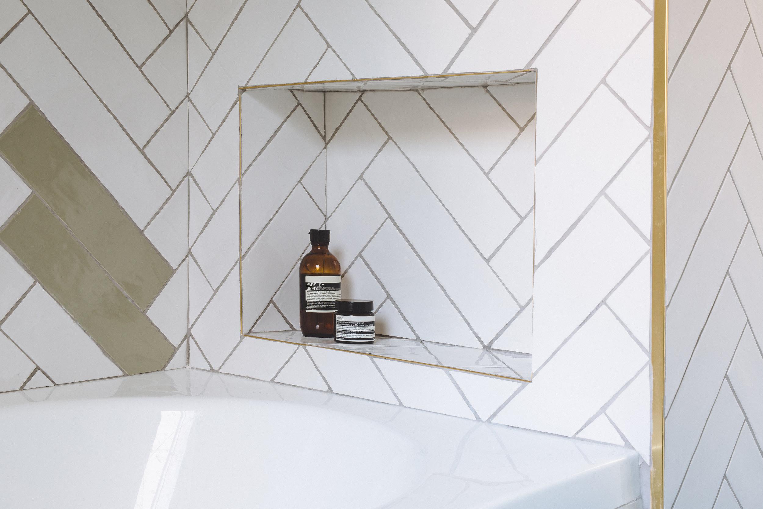 Bathroom subway tiles in fishbone. Brass details