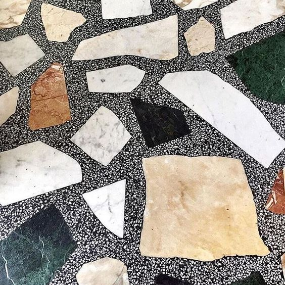 Large marble pieces in dark terrazzo surface