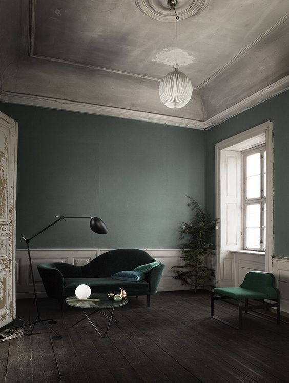 Green walls and light colored cornice in a classic space with a Scandinavian touch