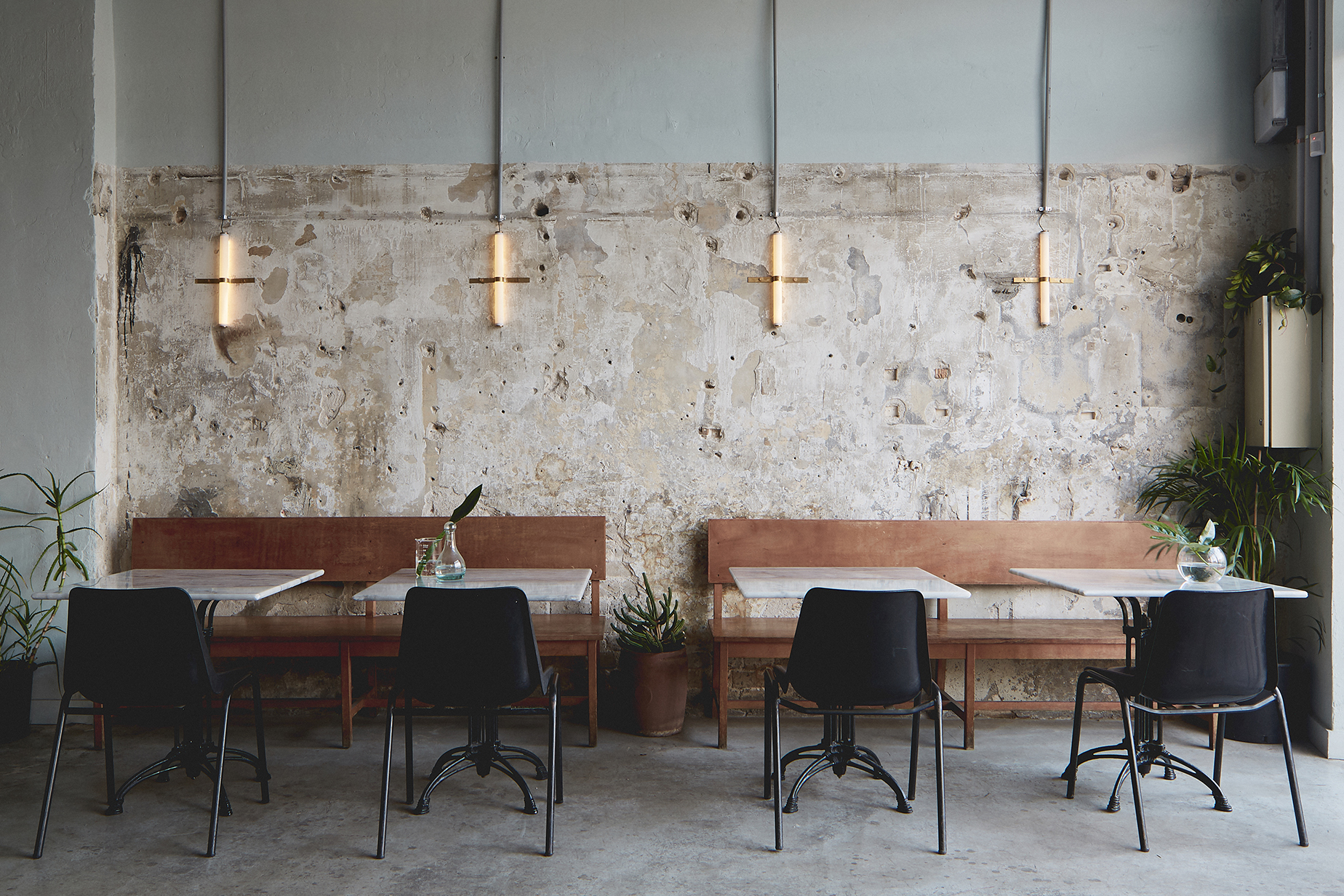 bare restaurant wall. wood benches and marble tables. tube lighting with brass detail