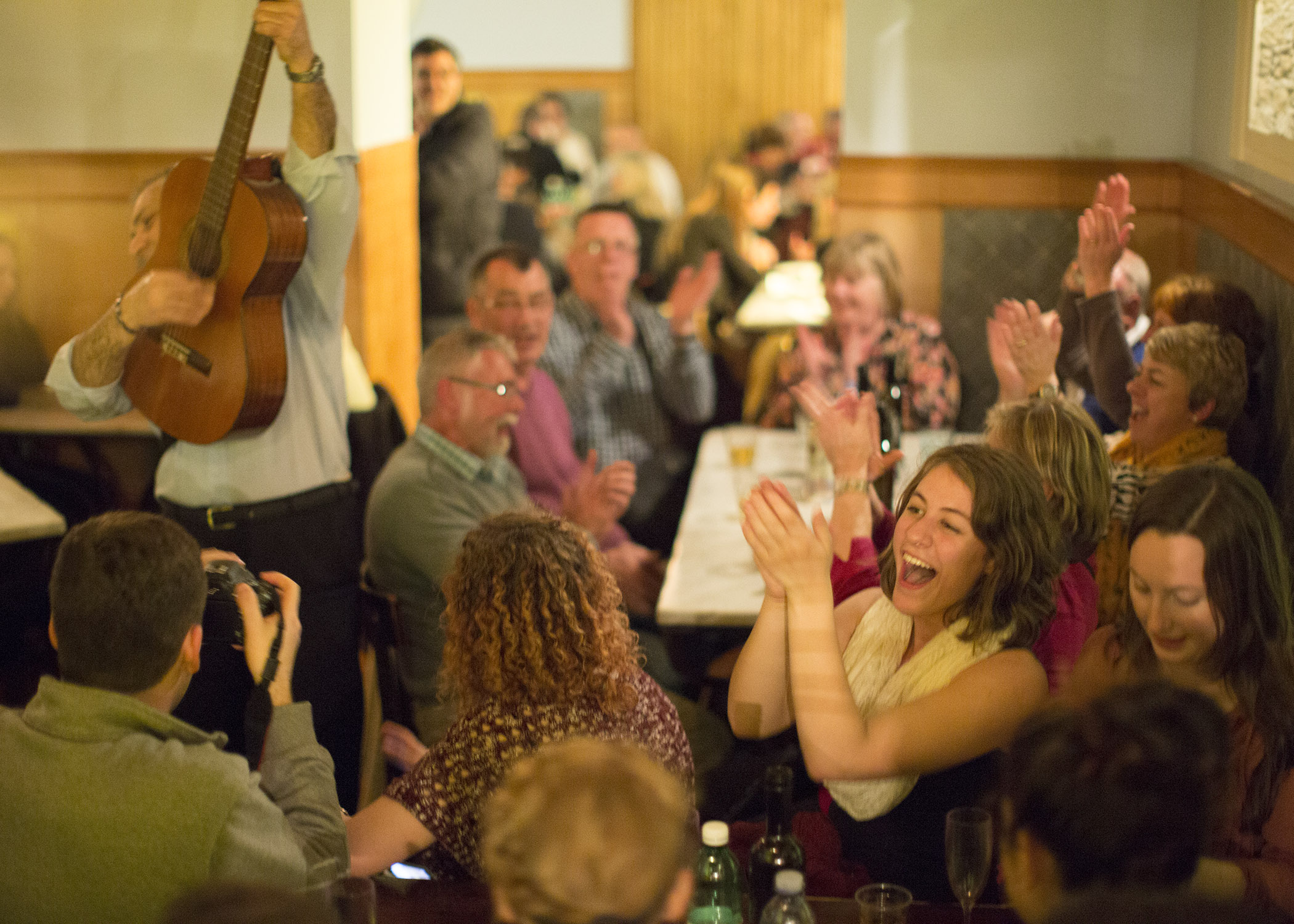Students interacting with locals and enjoying a musical performer in a neighborhood restaurant in Naples, Italy (photo: Canisius College)
