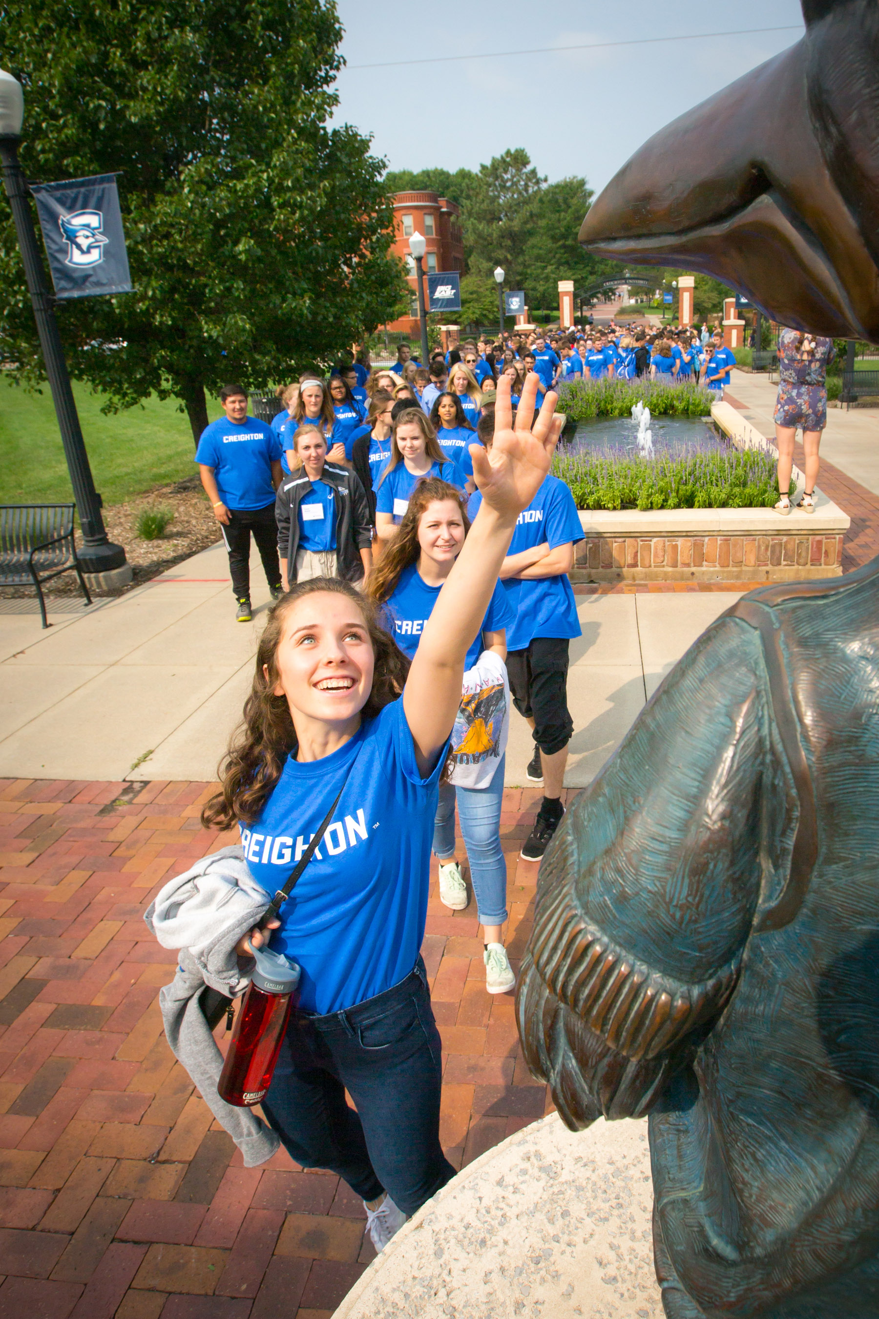 Creighton University students, all dressed in blue Creighton t-shirts, walked on the Creighton Pathway event, where they stopped to touch the beak of Billy Bluejay on their way to the Academic Convocation at the D.J. Sokol Arena (photo by Creighton University)
