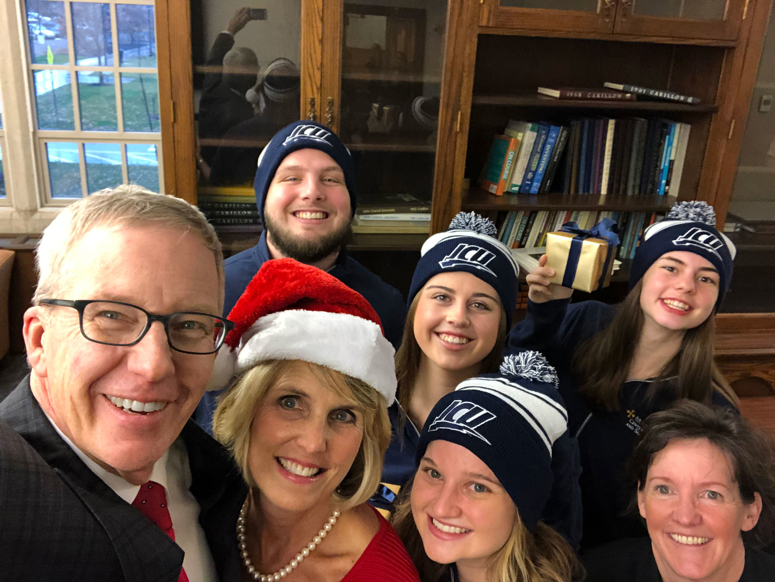 Dr. Michael Johnson, President of John Carroll University, took a holiday selfie with his wife, Jill, and Sr. Katherine Feely, director of the Center for Service and Social Action, with several students (photo by John Carroll University)