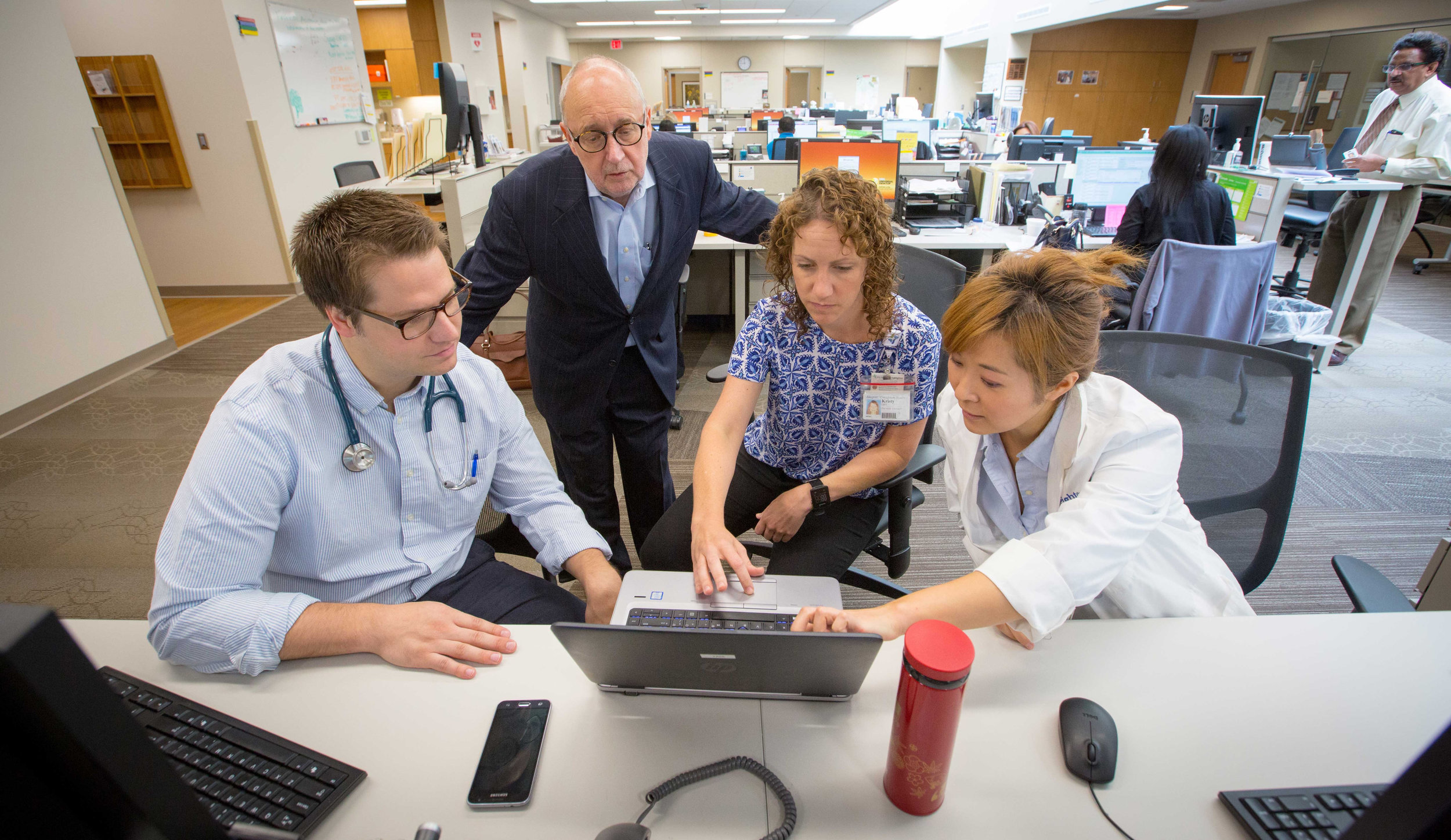"""At CHI Health Creighton University Medical Center, clinicians, residents and students gather in the """"huddle"""" as part of an innovative team-based approach. Team members from different health sciences backgrounds use their expertise for holistic health care (photo by Creighton University)"""