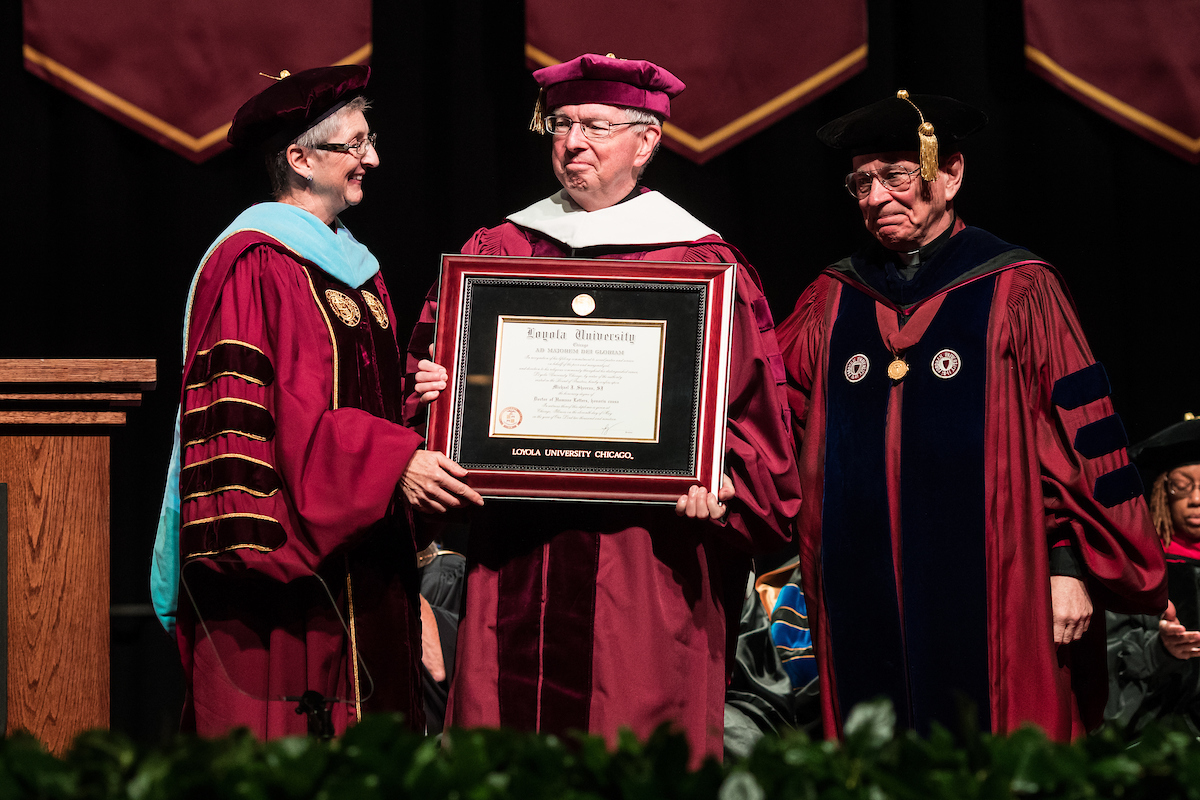 Rev. Michael J. Sheeran, S.J. receives his honorary degree from Jo Ann Rooney, JD, LLM, Ed.D., president of Loyola University Chicago, and Rev. Thomas J. Regan, S.J., Dean of the Graduate School and the College of Arts and Sciences at Loyola (photo by Lukas Keapproth)