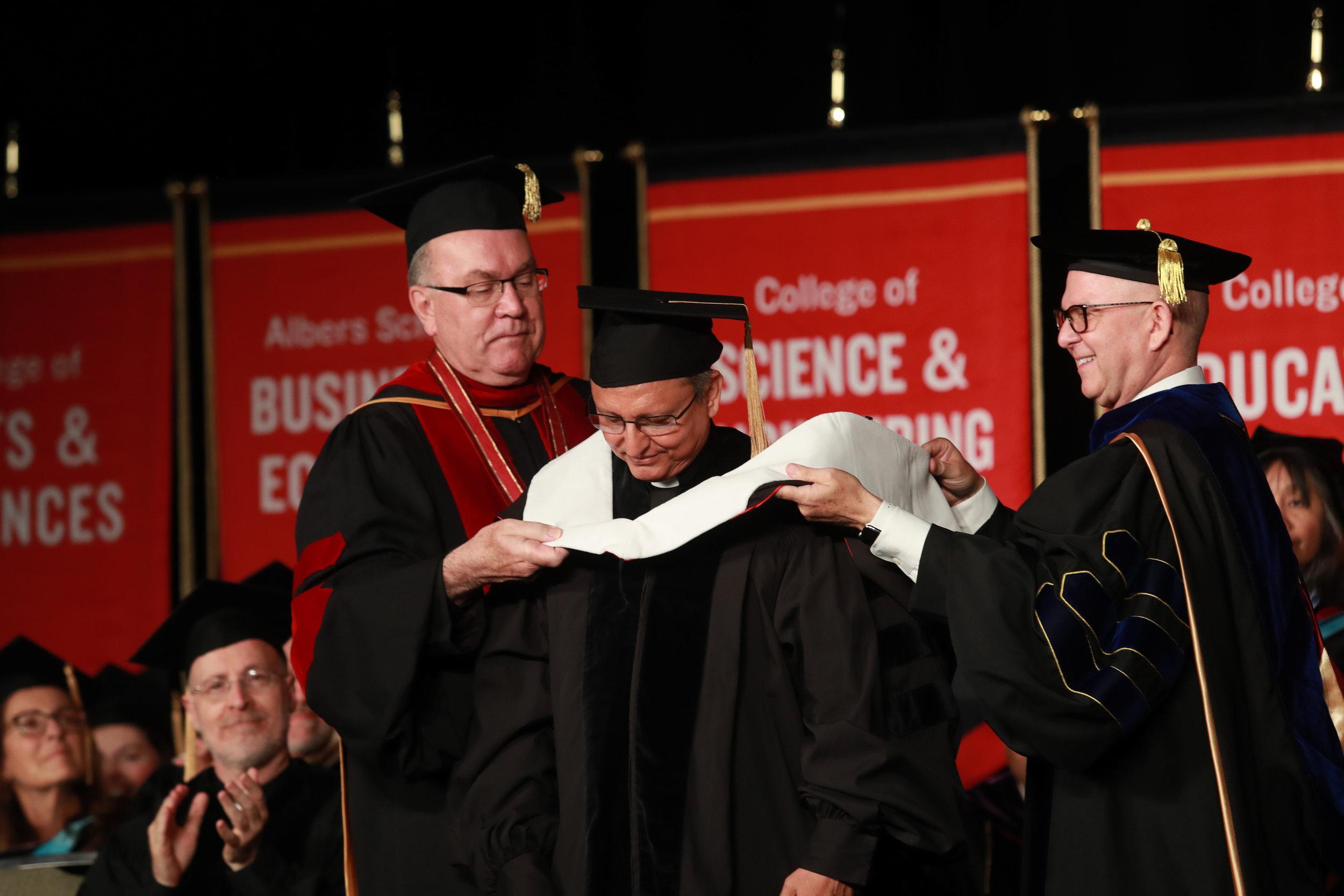 "Rev. Stephen Sundborg, S.J. (President of Seattle University) & Dr. Shane Martin (provost of SU) confer an honorary degree to Rev. José Alberto ""Chepe"" Idiaquez, S.J. (Photo by Seattle University/Yosef Kalinko)"