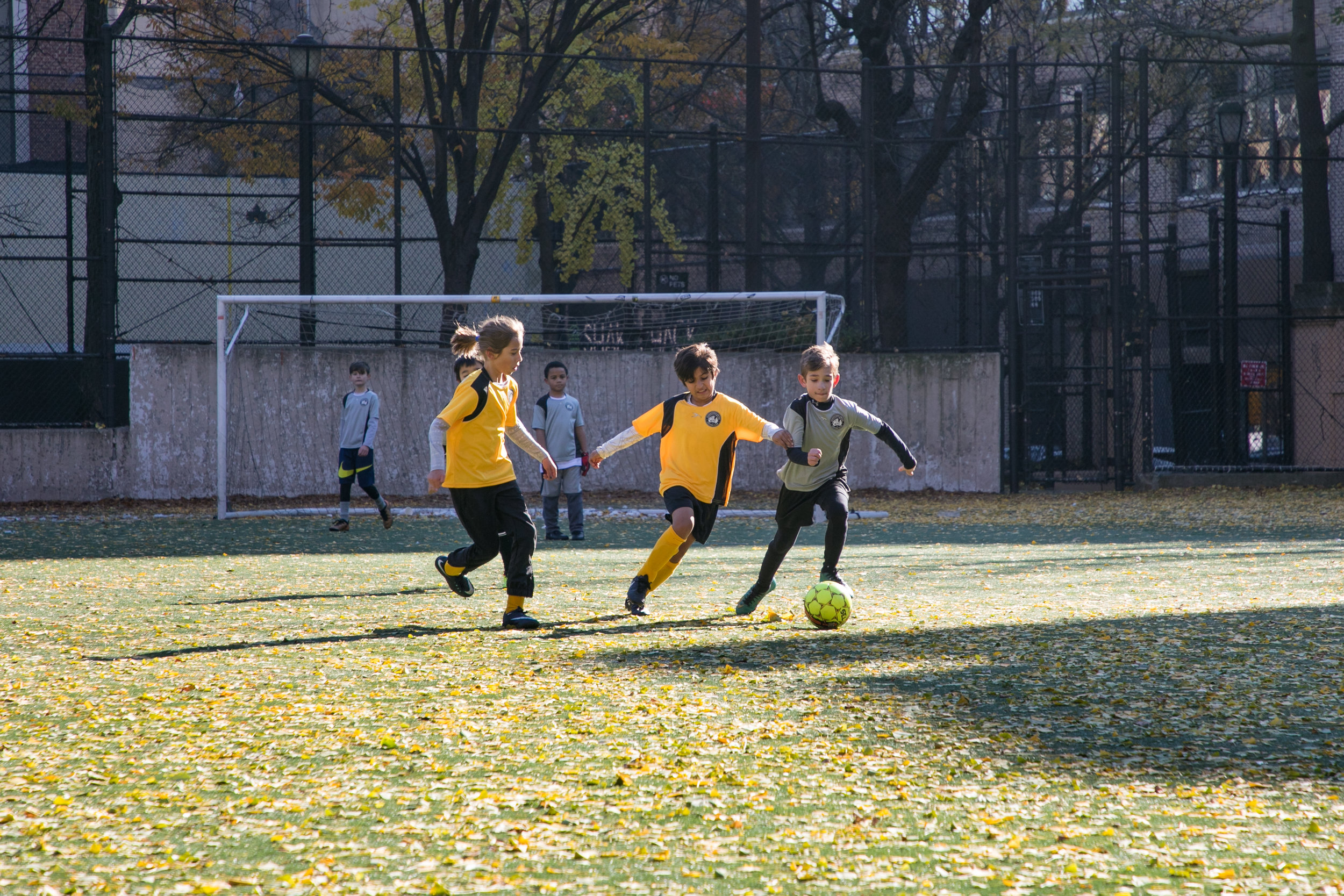 DUSC Recreation players fight for the ball, under the watchful eye of an older Travel player.