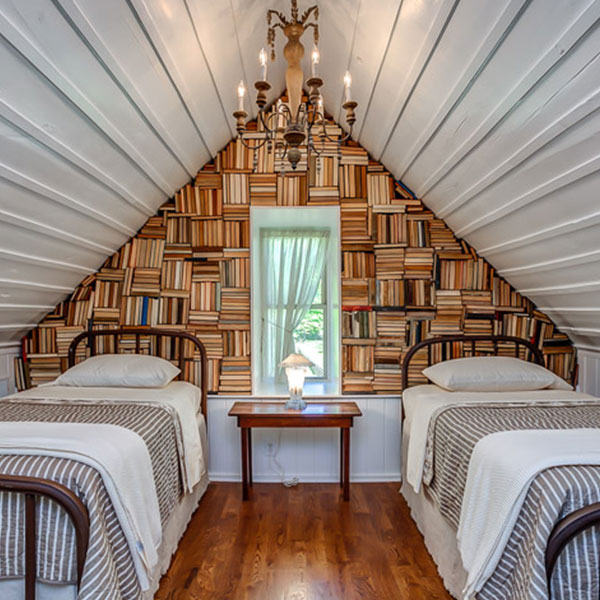 Wall built using antique books by City Farmhouse
