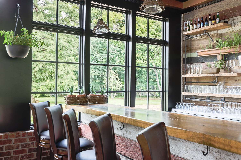 Leather bar stools provide comfortable seat at the bar at Homestead Manor | Interior Design: Kim Leggett | Photographer: Alyssa Rosenheck