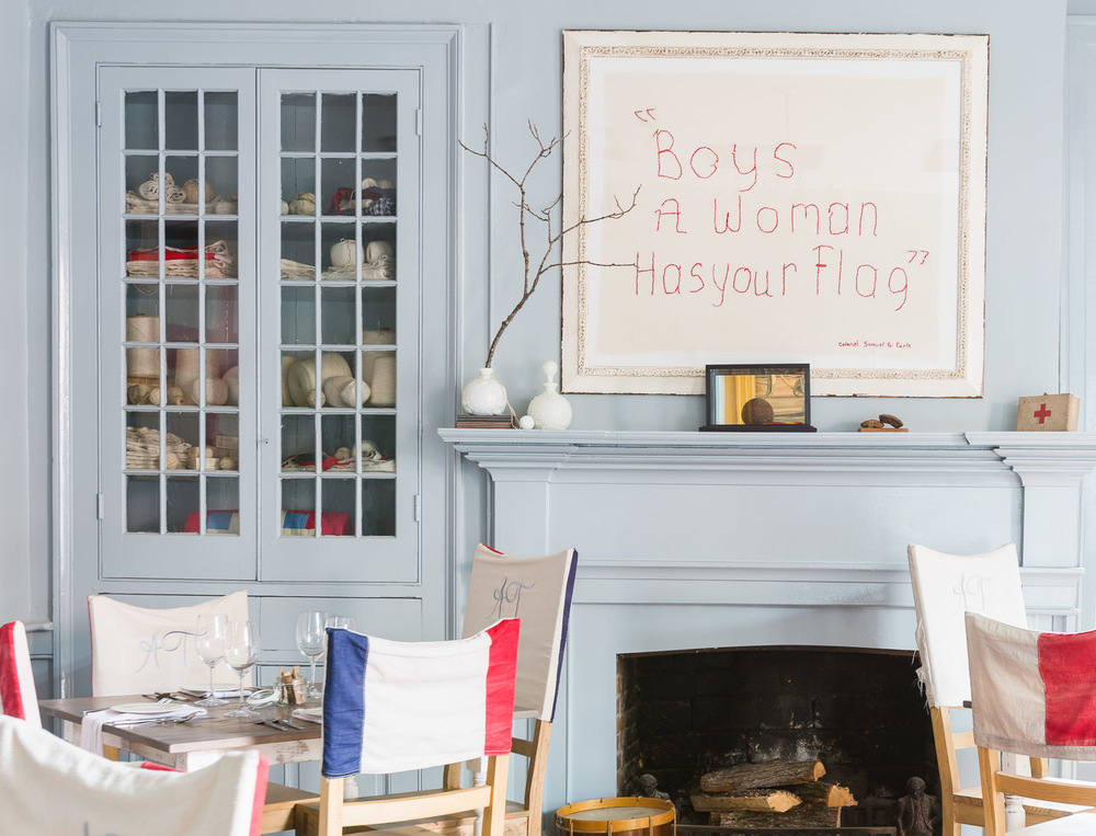 """Boys a women has your flag"" picture hangs above the fireplace 