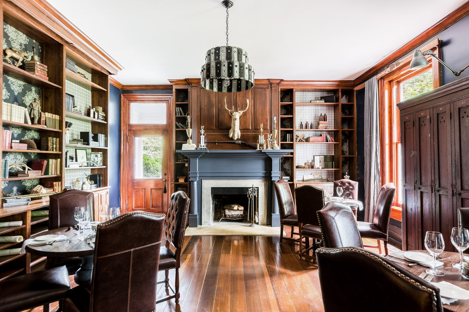 This cozy room has a library type feel with antique books and dark wood throughout | Interior Design: Kim Leggett | Photographer: Alyssa Rosenheck