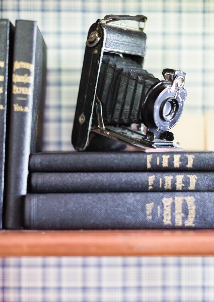 Antique camera on a shelf at Homestead Manor | Interior Design: Kim Leggett | Photographer: Alyssa Rosenheck