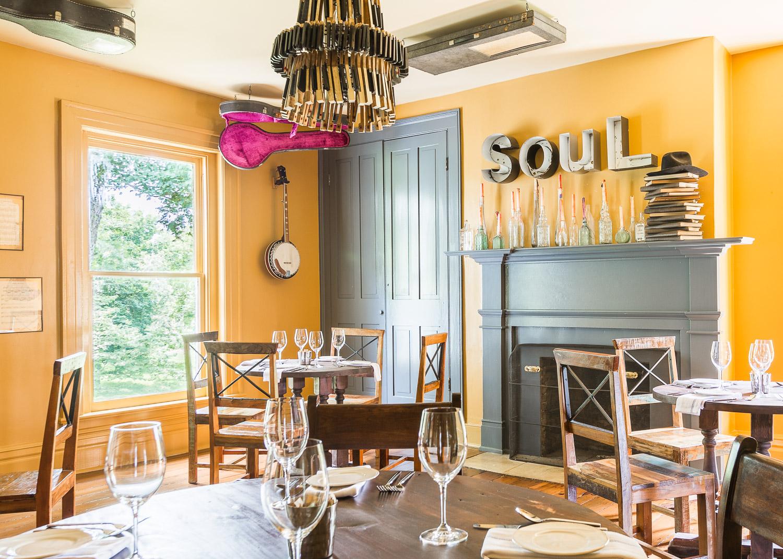 Bright yellow walls and eclectic decor fill this room at Homestead Manor | Interior Design: Kim Leggett | Photographer: Alyssa Rosenheck