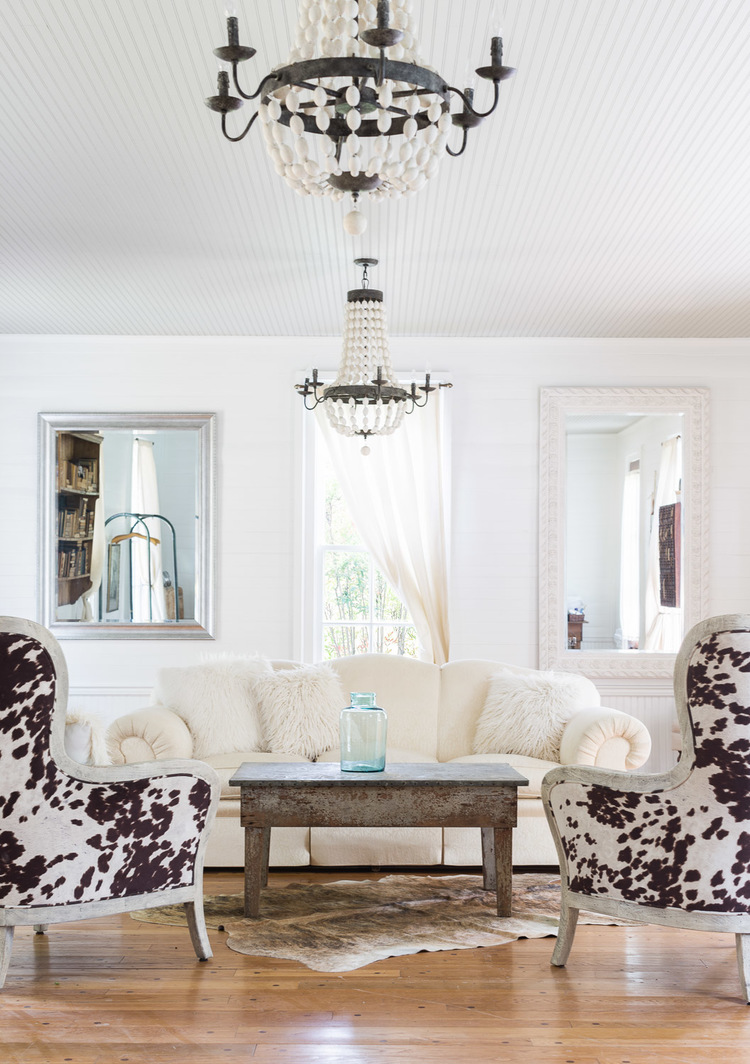 Decorated in Modern Farmhouse Style boasting antique chandeliers, cowhide covered chairs, and other antique furnishings. Interior Design: Kim Leggett, City Farmhouse