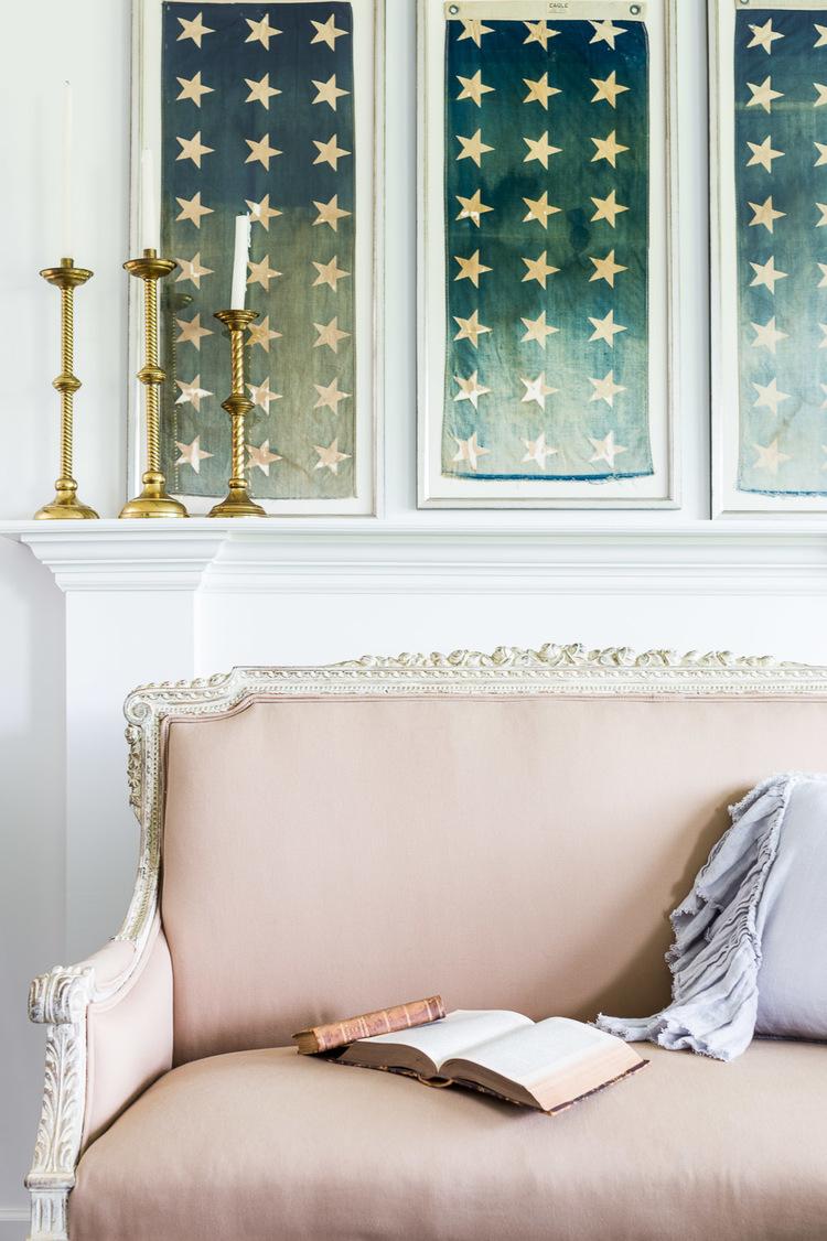 Three framed flags hang above the fireplace at One King's Lane   Photography: Alyssa Rosenheck   Interior Design: Kim Leggett
