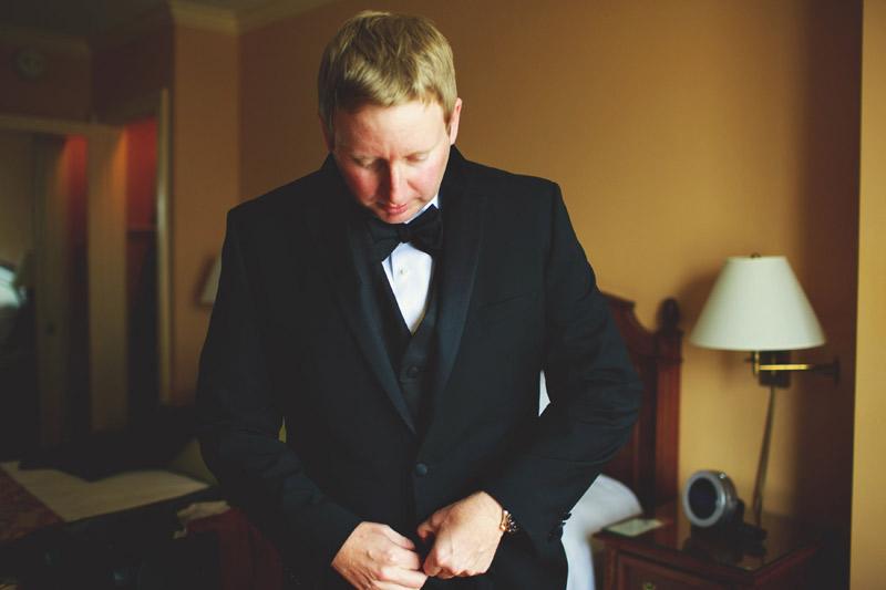 ringling museum wedding: groom putting on jacket