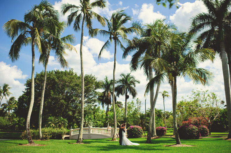 naples backyard beach wedding: bride and groom hugging under palm trees