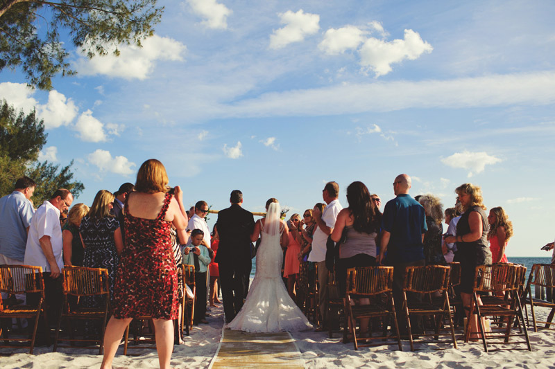 naples backyard beach wedding: bride walking down isle
