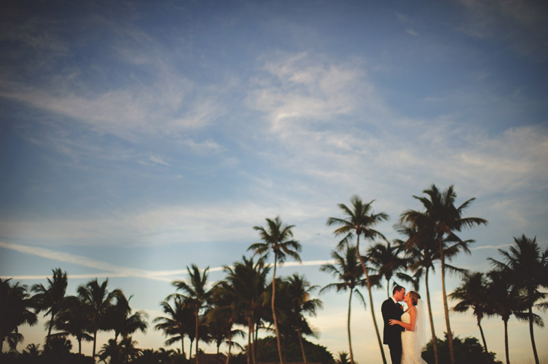 naples backyard beach wedding: bride and groom kissing near palm trees