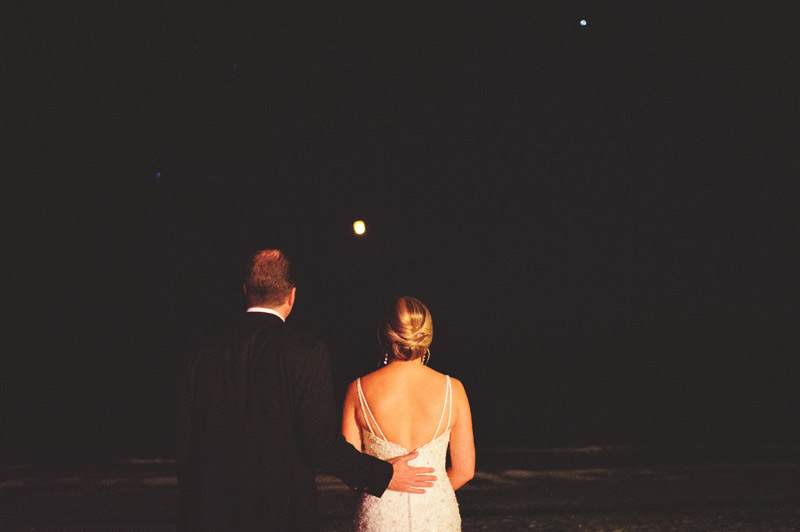 naples backyard beach wedding: lantern release bride and groom watching