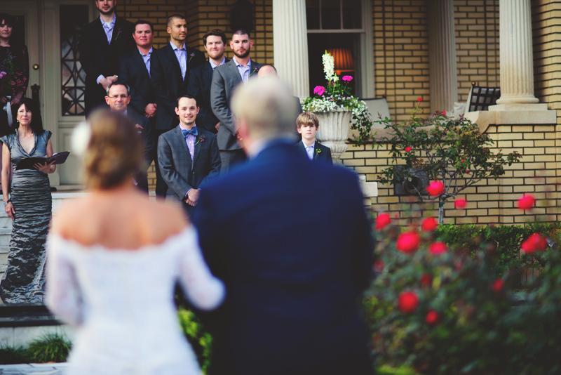 backyard wedding tampa: grooms smiling while bride is walking down aisle