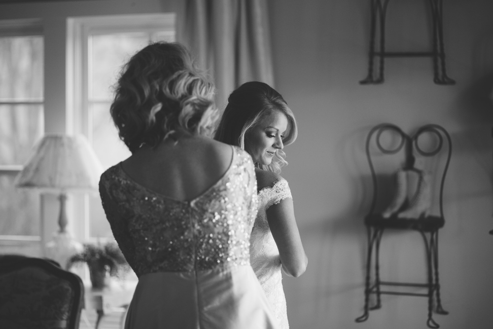 mint springs farm wedding: mother helping bride get into dress