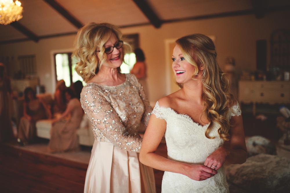 mint springs farm wedding: bride getting into dress