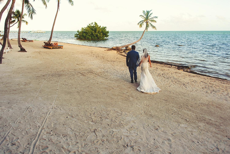 pierre's restaurant wedding: bride and groom walking on beach