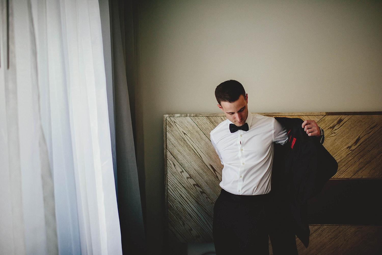 groom putting on hugo boss jacket