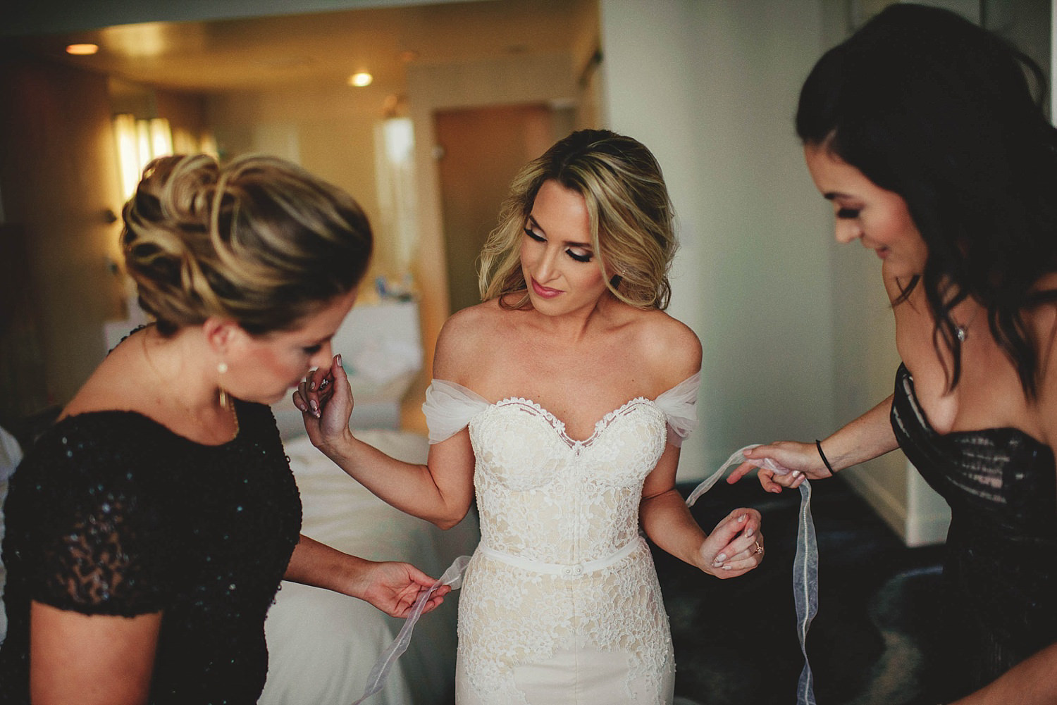 bridesmiads helping bride with dress