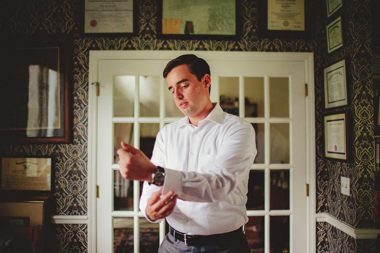 knowles memorial chapel wedding: Groom putting on cufflinks