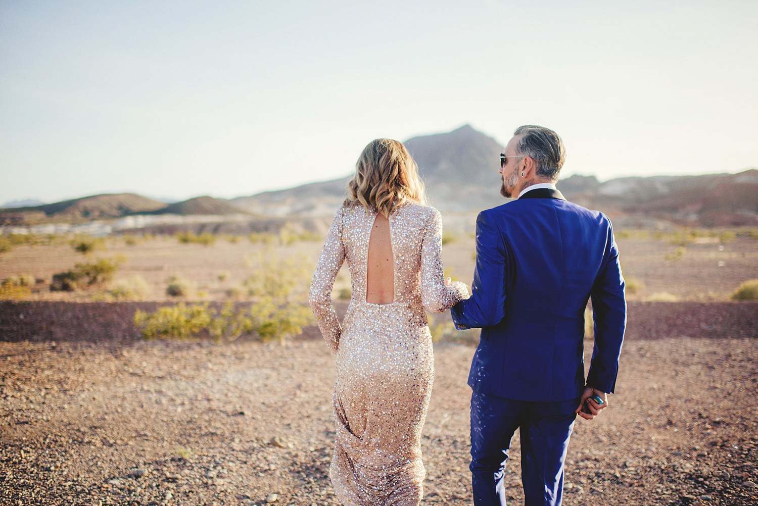 neon museum wedding - bride and groom walking thru desert