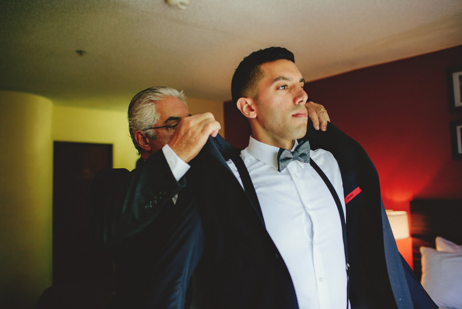 editorial ringling wedding: dad helping put on grooms jacket