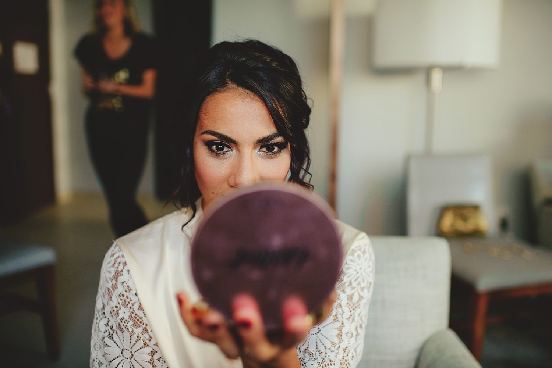 bride looking into makeup mirror
