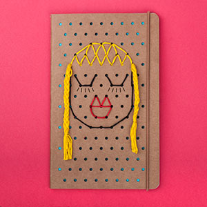 Loose threads are braided and eyelashes drawn on the cover.