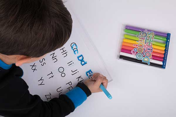 4 year old tracing the alphabet onto a piece of acrylic with Oodles of Doodles Markers