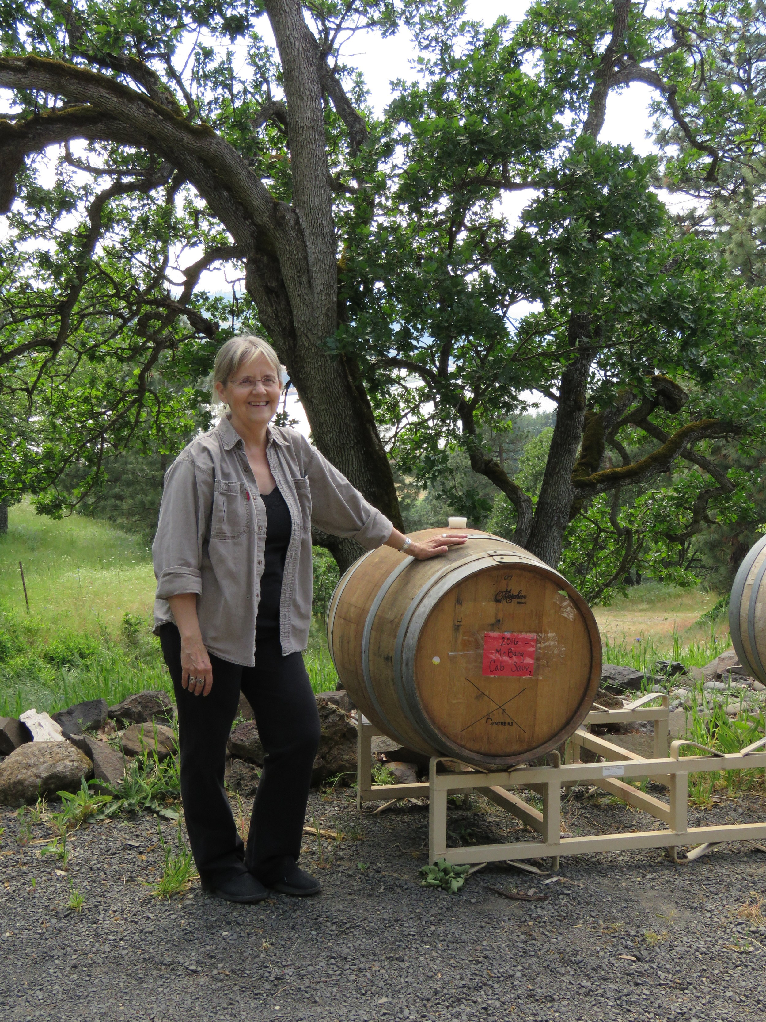 Sue posing next to an emptied barrel of wine after a hard day of work