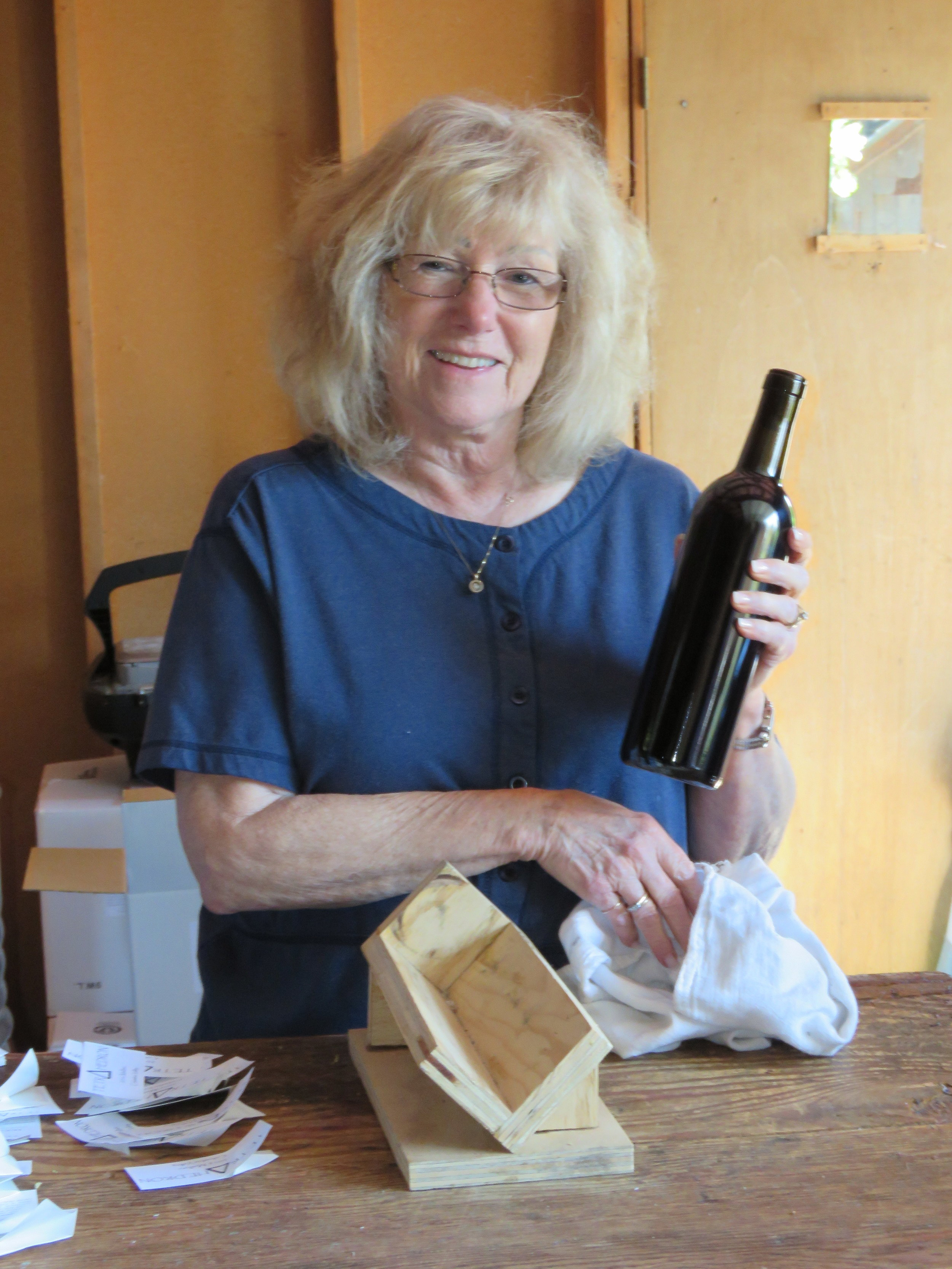 Bonnie wiping down a bottle before adding the wine labels
