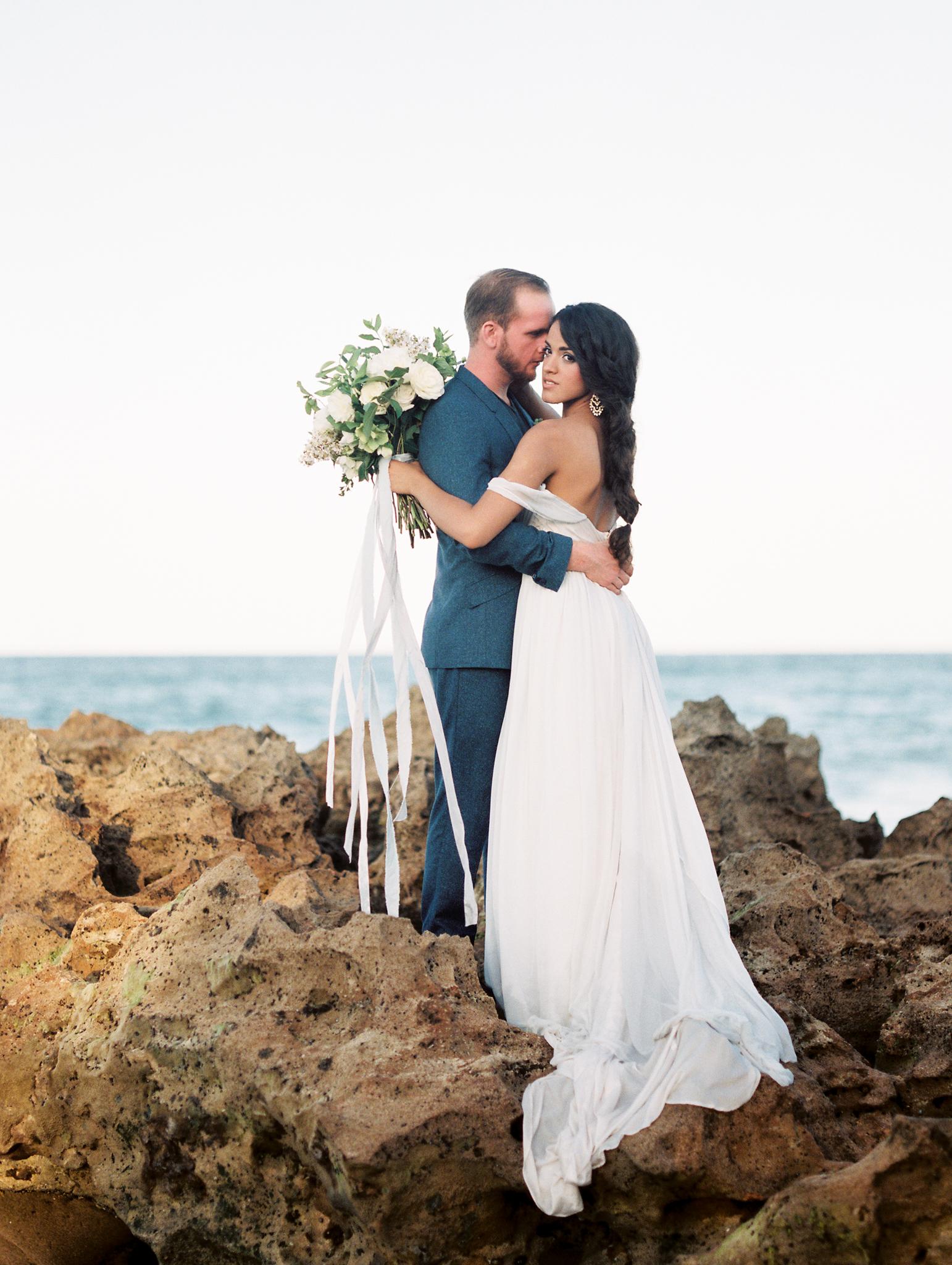 coral cove, jupiter beach FL, palm beach wedding photos, bride and groom on rocks on beach photos