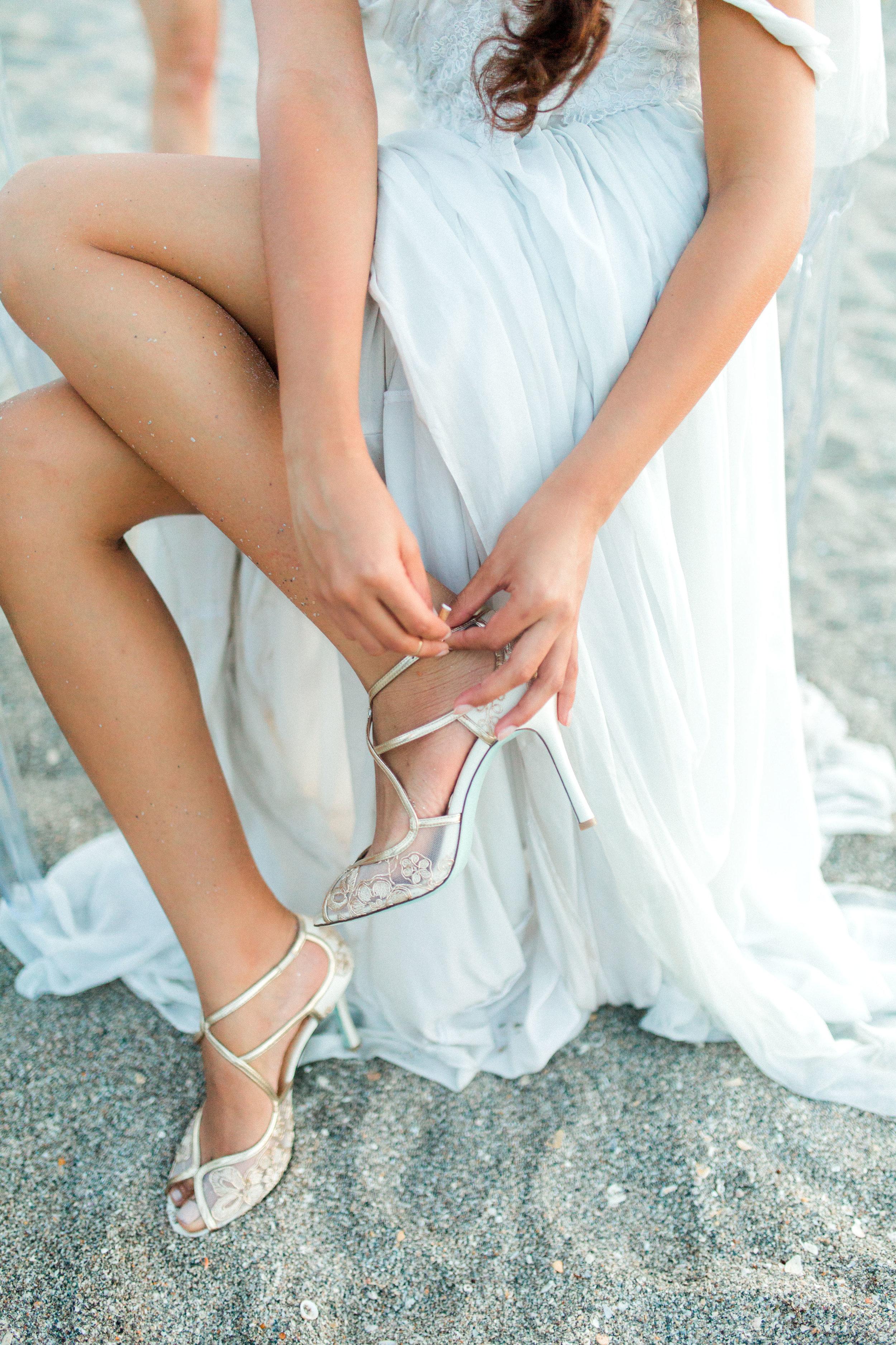 coral cove, jupiter beach FL, palm beach wedding photos, bride putting on shoes