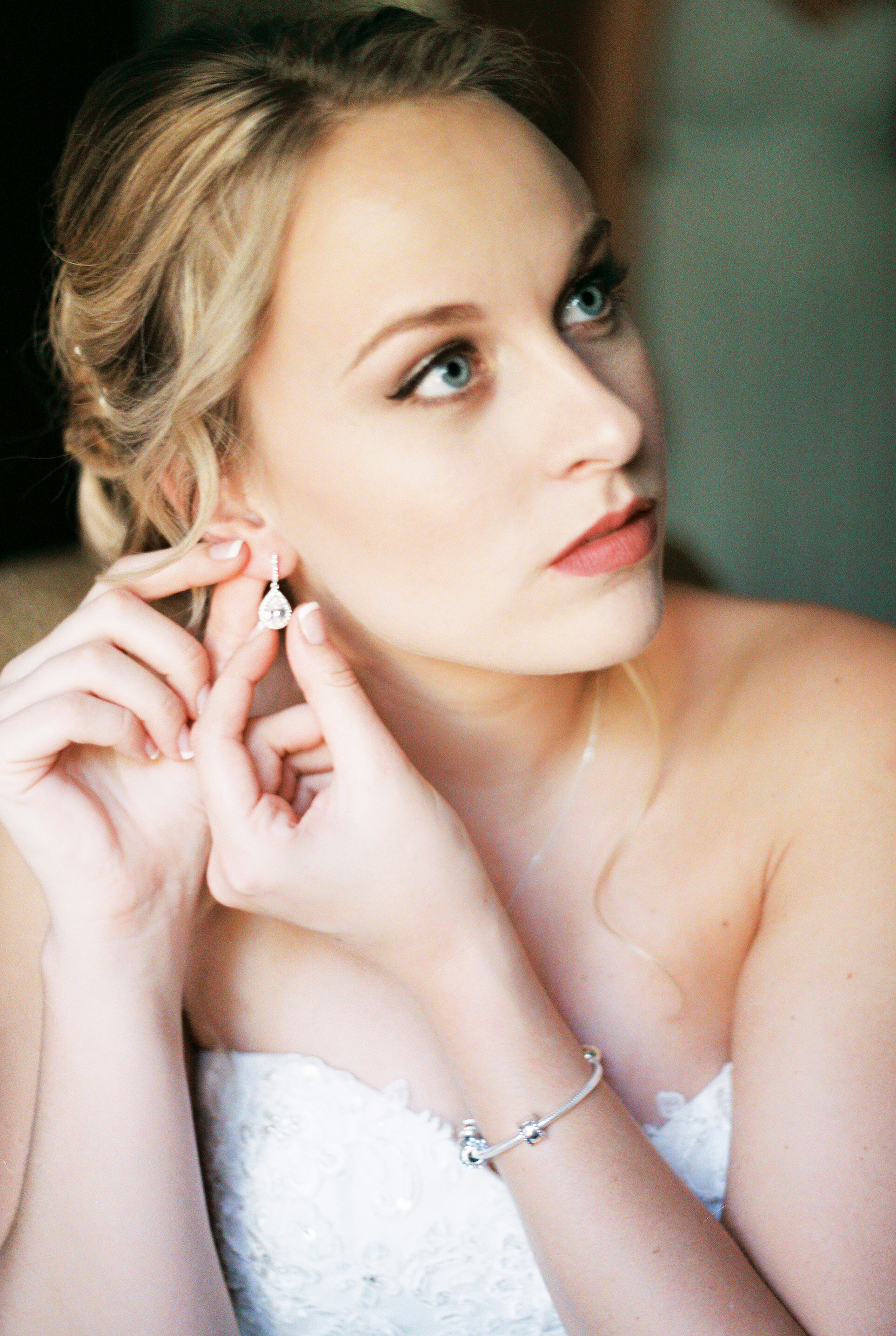 lake-mary-events-center-Florida-wedding-photos-bride-putting-on-earrings-jewelry