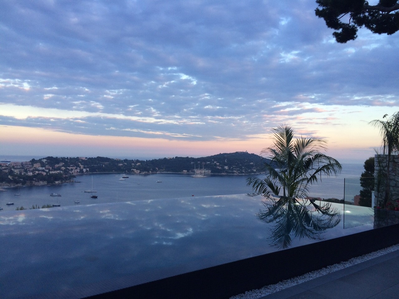 The ocean view beyond the infinity mirror pool from the villa terrace
