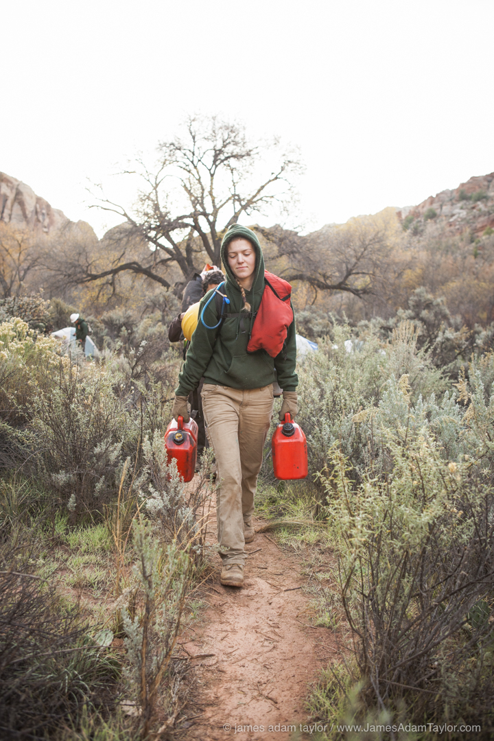 Boulder B Crew member Sophia Knaphus carrying fuel and bar oil to the days work site.