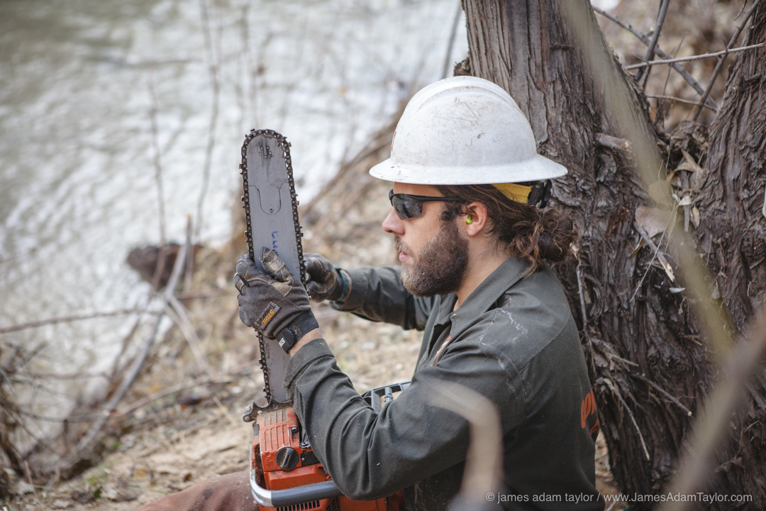 Boulder B Crew leader, James Shaw sharpening chainsaw teeth along the bank of Boulder Creek.